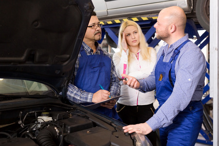 specialists: Portrait worried young woman and specialists at auto repair shop. Focus on the left man