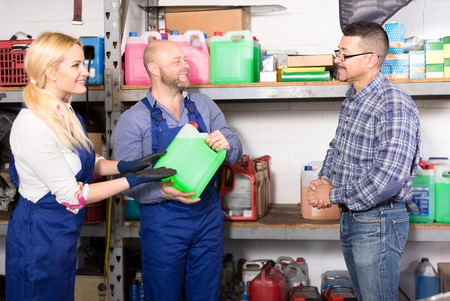 antifreeze: Automotive shop workers are selling antifreeze liquid to a customer