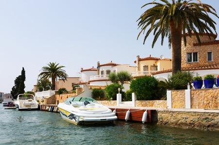 waterways: EMPURIABRAVA, SPAIN - MAY 14, 2015: Homes at residential marina. Empuriabrava  is  largest residential marina in Europe with some 24 km of navigable waterways