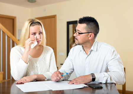 spouses: Upset spouses having financial problems. Sad wife and husband sitting at the table and looking at a pile of documents