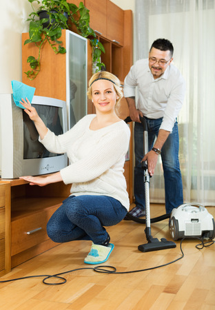 dusting: Smiling spouses dusting and hoovering at domestic interior Stock Photo