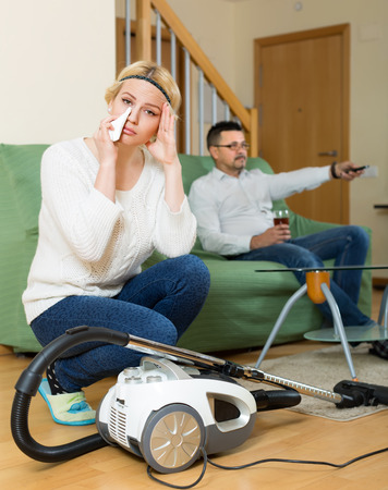 sobbing: Man resting on sofa with beverage, his unhappy young wife cleaning around