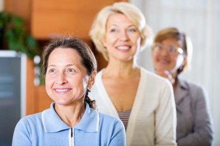 mature women: Three smiling mature women posing at home interior Stock Photo