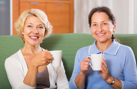 Smiling positive female pensioners drinking tea on sofa at home. Focus on blonde photo