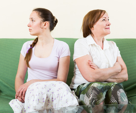 homily: Mature mother and  daughter  after quarrel  in  living room