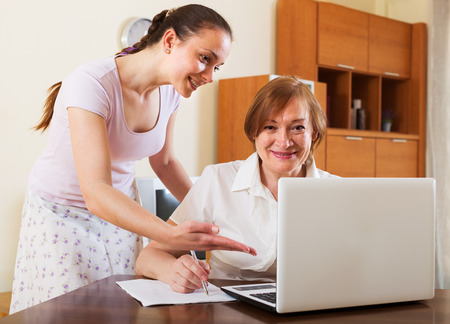 parsimony: Smiling women looking financial documents in laptop at table in home interior