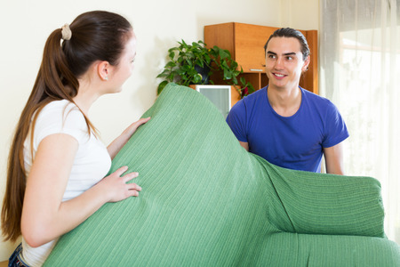 transposition: Happy couple doing relocation of furniture at living room Stock Photo