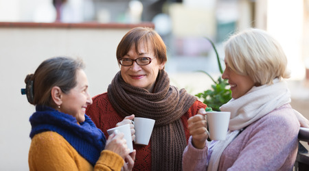 woman drinking coffee: Portrait of smiling senior female friends drinking coffee at patio