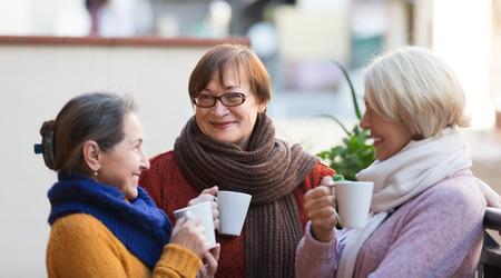 mujer tomando cafe: Retrato de la sonrisa altos amigas beben el café en el patio