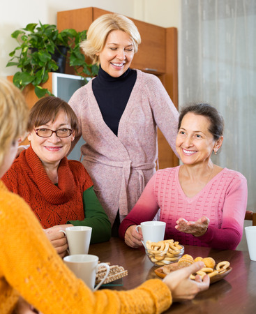 talkative: Smiling female pensioners drinking coffee and talking at home Stock Photo
