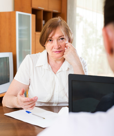 census: Mature woman answer questions of worker at table in home or office