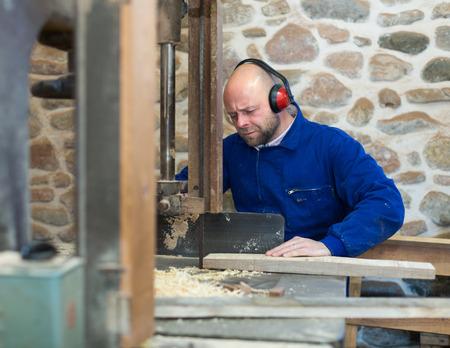 woodcutting: Professional craftsman working on a woodcutting machine at guitar workshop