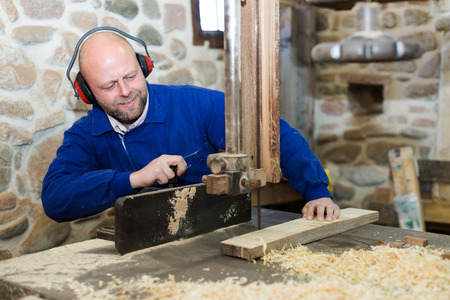 woodcutting: Positive craftsman working on a woodcutting machine at guitar workshop