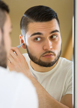 trimmer: Guy using trimmer for removing hair in his ear in front of a mirror Stock Photo