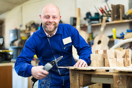 workplace wellness: Smiling male craftsman working with unfinished guitar indoors