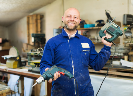 woodworker: Happy adult professional woodworker on lathe at musical instrument workroom Stock Photo