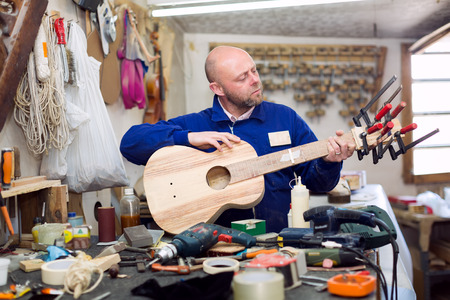 workplace wellness: Focused man is creating a guitar in a workshop full of instruments to process wood
