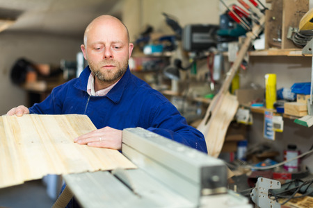 woodworker: Portrait of professional woodworker working on a machine at wood workshop Stock Photo