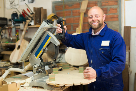 woodworker: Smiling adult professional woodworker on lathe at musical instrument workroom