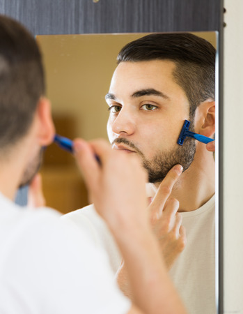 russian man: russian man looking at mirror and shaving face with razor