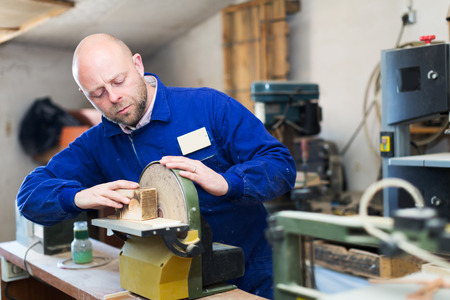 toolroom: Portrait man craftsman working with unfinished guitar indoors