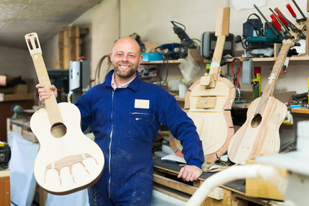 toolroom: Successful adult atelier posing with his guitars at workshop