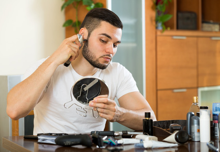 shave: American man shaving face with electric razor Stock Photo