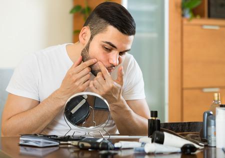 espejo: Chico de 20 a�os mirando al espejo y hacer estallar una espinilla