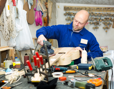 adult male: Concentrated adult male craftsman working with unfinished guitar indoors