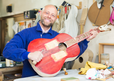 atelier: Happy atelier posing with his guitars at workshop