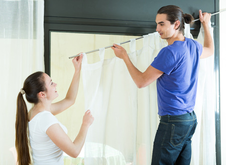 Happy american young couple hangs curtains  on window