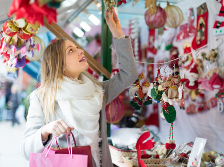 outwear: Portrait of female customer in casual outwear near counter with Christmas gifts Stock Photo