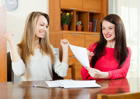 Happy women with financial documents  at table photo