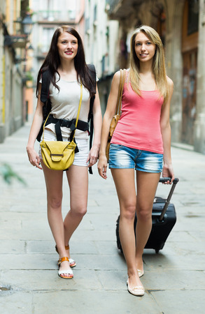 Two smiling young women with luggage walking through city street photo