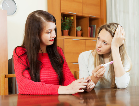 worried women with pregnancy test at table in home photo