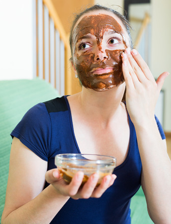 Young woman applying mask on her face on sofa photo