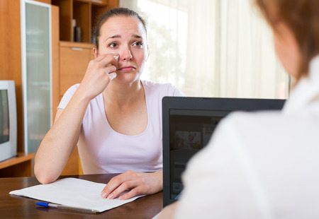 rapacity: woman answer questions of worker at table in home Stock Photo