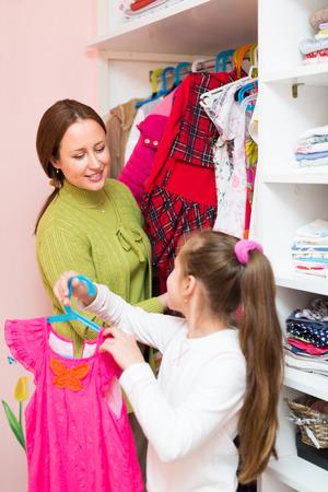 cloakroom: Happy preschooler smiling girl with mom choosing apparel in cloakroom