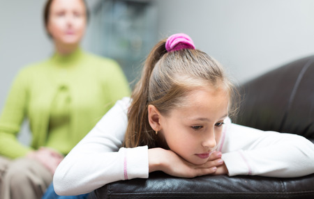 padres hablando con hijos: Mujer enojada regaños pequeña hija en el interior casero Foto de archivo