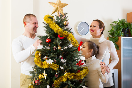christmas tree: Parents and their child preparing for Christmas at the living room Stock Photo