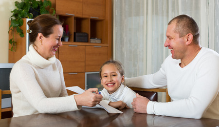 social problems: Happy parents and child with documents at table in the living room Stock Photo
