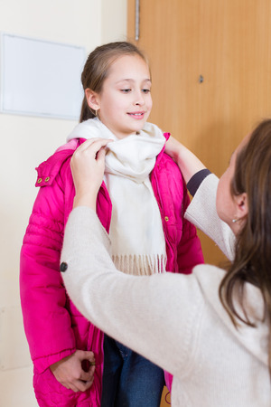 warmly: Careful woman dressing her daughter warmly before off