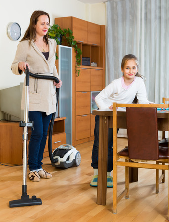 Smiling girl dusting and her mother vacuuming at home. Focus on girl photo
