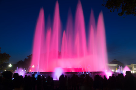 gazer: Evening view at colorful vocal fountain Montjuic show and people watching it nearby in Barcelona.