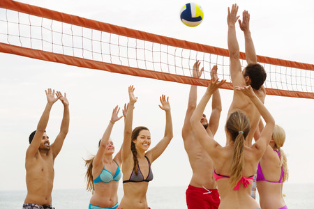 Happy young friends playing volleyball at sandy beach photo