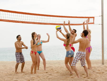 freetime: Young group of friends having fun at beach and playing ball Stock Photo