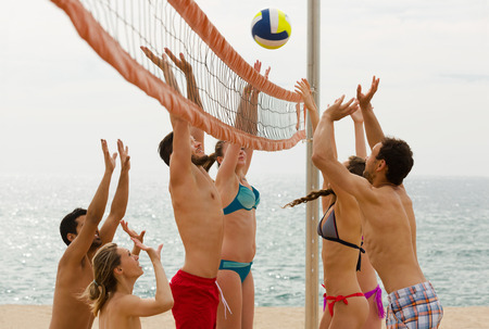 smiling american adults throwing ball over net and laughing photo