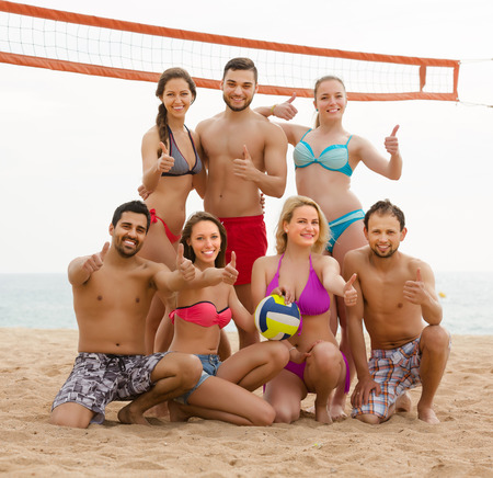 Portret of happy friends playing volleyball at sandy beach photo