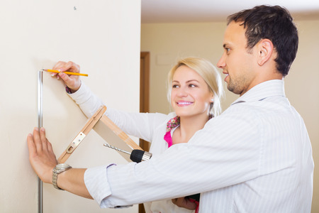modifying: Man and smiling woman choosing place for shelf at home