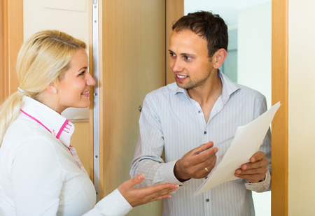 communal: Communal services employee asking tenant to sign a document at doorway Stock Photo